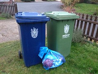 blue recycling bags on a lawn next to bins